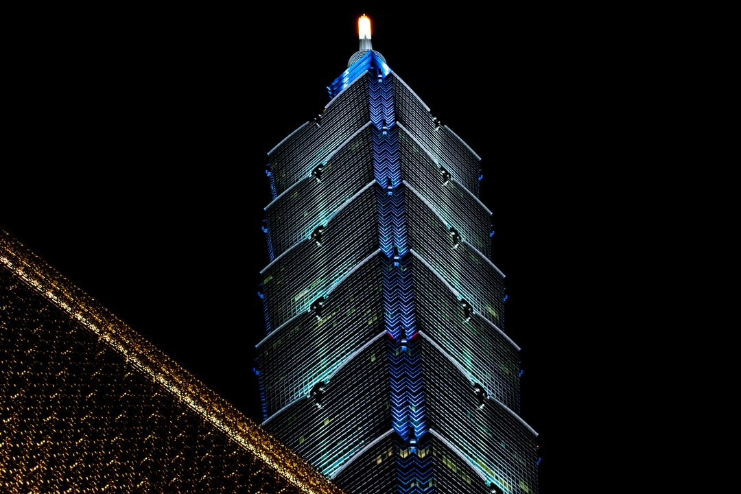 A tall building lit up at night with Bank of China Tower in the background