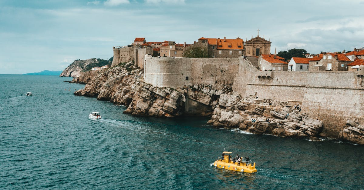 A small boat in a large body of water with Dubrovnik in the background