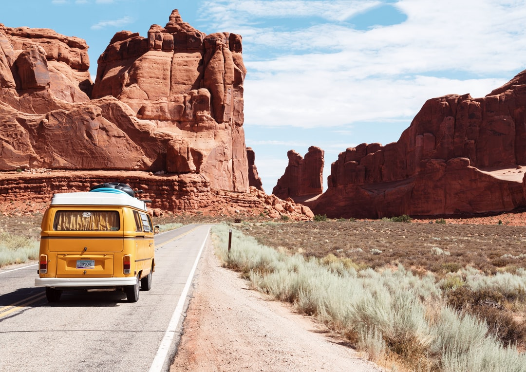 A bus that is parked on the side of Arches National Park